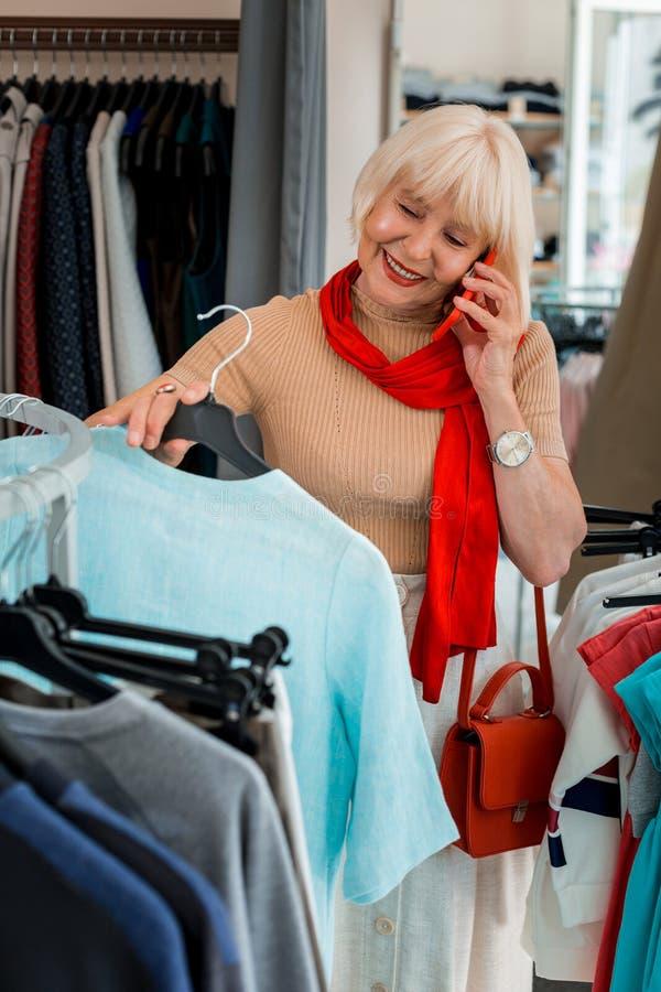 Frohe ältere Frau, die Sommerkleid bei der Unterhaltung über Handy wählt lizenzfreies stockbild