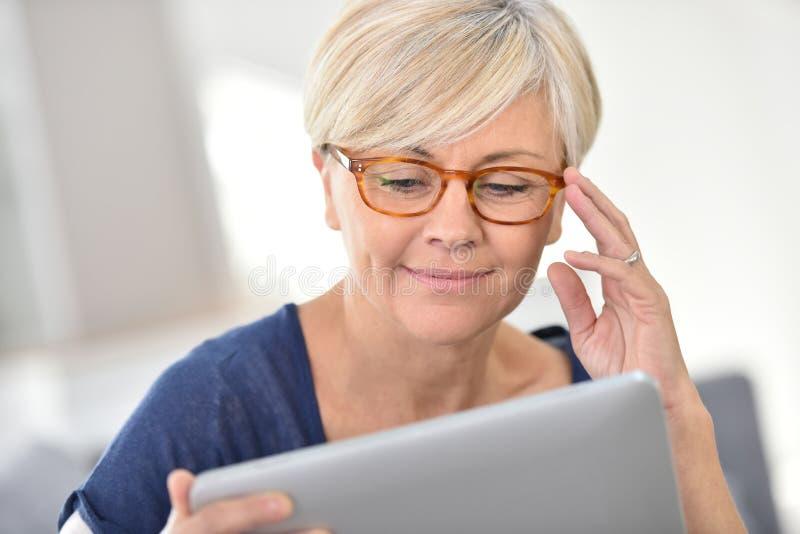 Frohe ältere Frau, die Tablette verwendet stockfoto