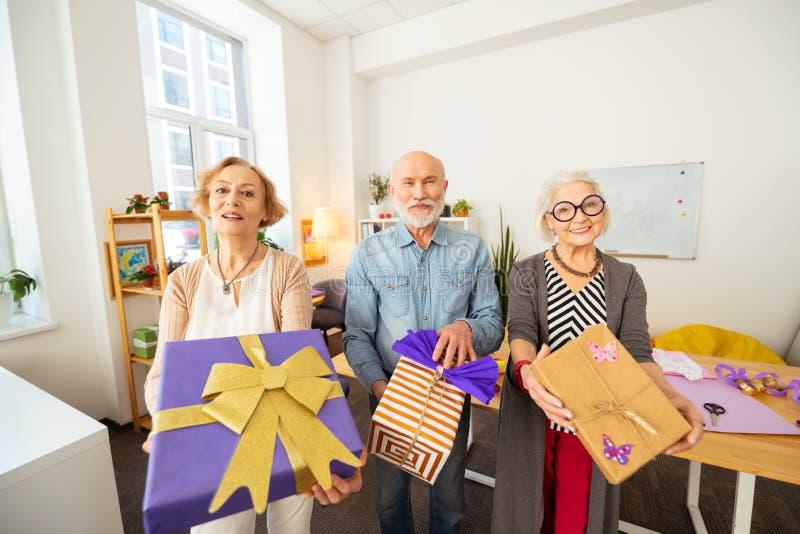 Frohe ältere Menschen, die Ihnen ihre Geschenke zeigen lizenzfreie stockfotos