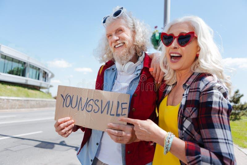 Frohe ältere Paare, die nach einer Fahrt suchen lizenzfreies stockfoto