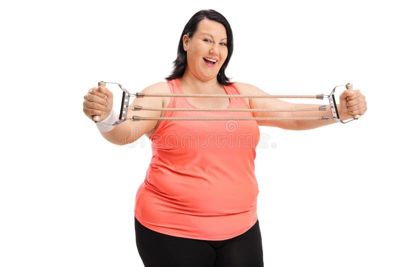Frohe überladene Frau, die mit einem Widerstandband trainiert stockbilder