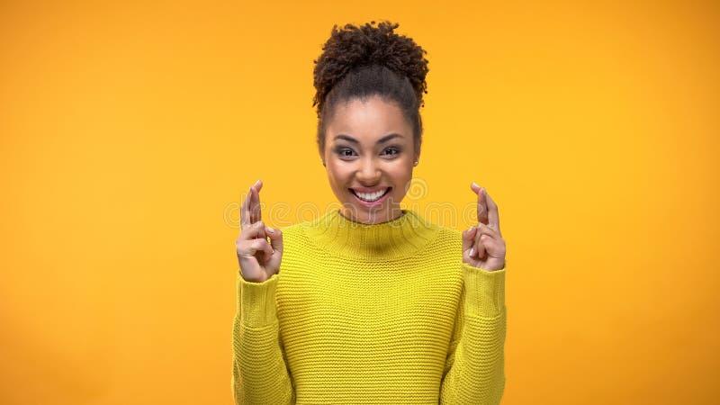 Frohe afrikanische Frau, die Wunsch, Kreuzungsfinger für gutes Glück, Hoffnungssymbol macht stockfotografie