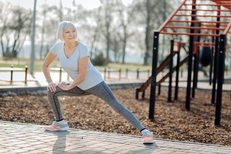 Frohe alte Frau, die draußen trainiert lizenzfreies stockbild