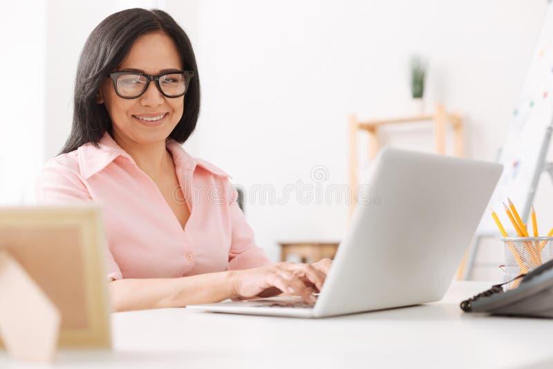 Frohe asiatische Frau, die im Büro arbeitet lizenzfreies stockbild