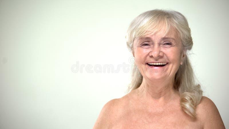 Frohe attraktive Frau, die, Patient zufrieden gewesen mit skincare Verfahren lacht stockbilder