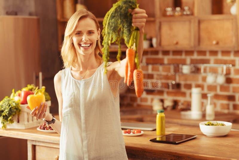 Frohe Blondine, die organische Karotte demonstriert lizenzfreie stockfotos