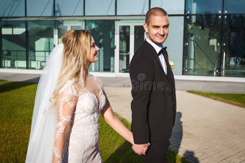 Frohe Braut und Bräutigam, die nahe dem modernen Gebäude geht stockfoto
