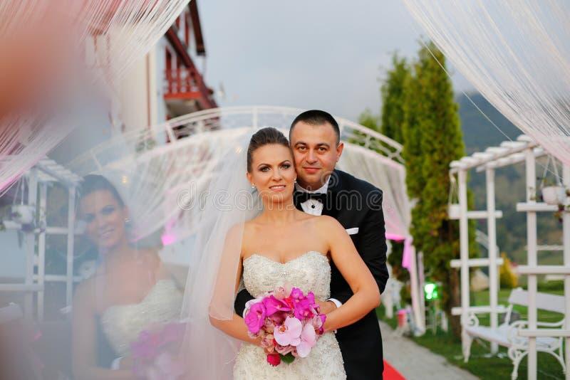 Frohe Brautpaare, die am Hochzeitstag umfassen lizenzfreie stockfotografie