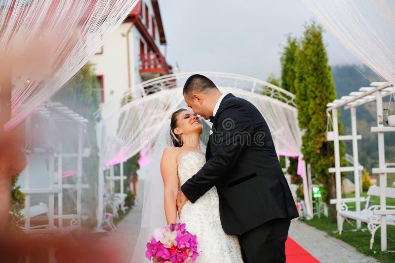 Frohe Brautpaare, die am Hochzeitstag umfassen lizenzfreies stockbild