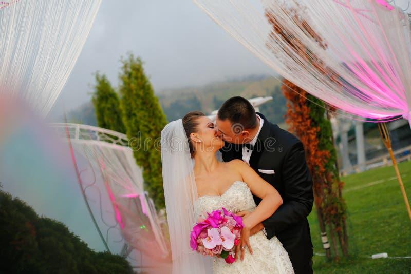 Frohe Brautpaare, die am Hochzeitstag umfassen lizenzfreie stockfotos