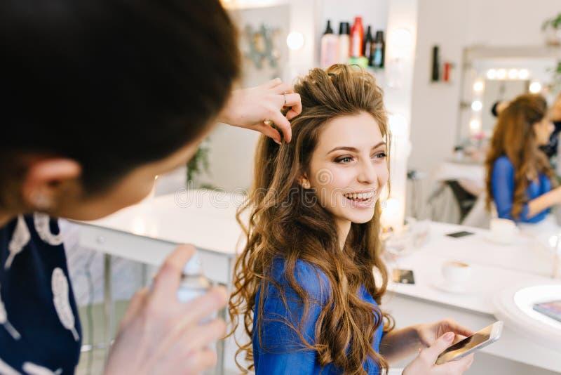Frohe brunette junge Frau w?hrend der Vorbereitung zur Partei im Friseursalon Herstellung der stilvollen Frisur, Frisur, wahr stockbilder