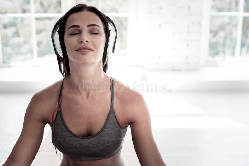 Frohe Dame, die Musik während der Meditation hört stockfoto