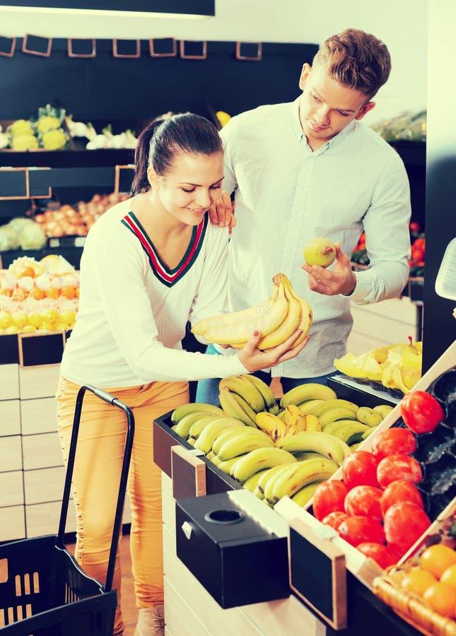 Frohe erwachsene Paare, die auf Früchten im Shop entscheiden stockbilder