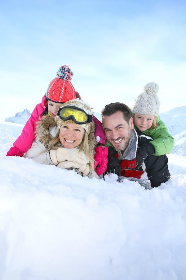 Frohe Familie, die das Lügen im Schnee genießt stockfotos