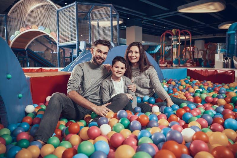 Frohe Familie, die im Pool mit Bällen sitzt lizenzfreies stockfoto