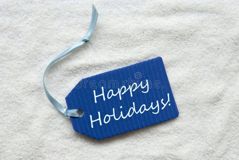 Frohe Feiertage auf blauem Aufkleber-Sand-Hintergrund stockbilder