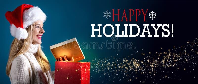 Frohe Feiertage Mitteilung mit der Frau, die eine Geschenkbox öffnet stockbild