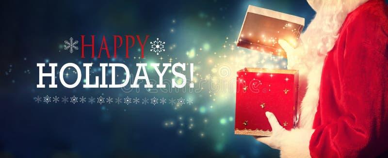 Frohe Feiertage Mitteilung mit Sankt, die eine Geschenkbox öffnet stockfotos