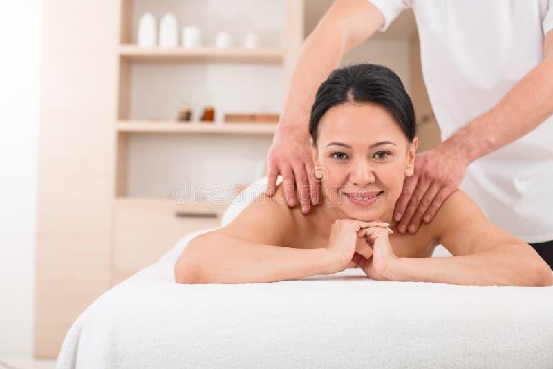 Frohe Frau, die eine Massage am Badekurort erhält stockbild