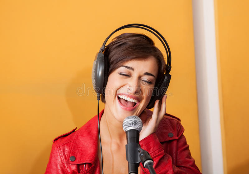 Frohe Frau, die im Tonstudio singt stockfoto