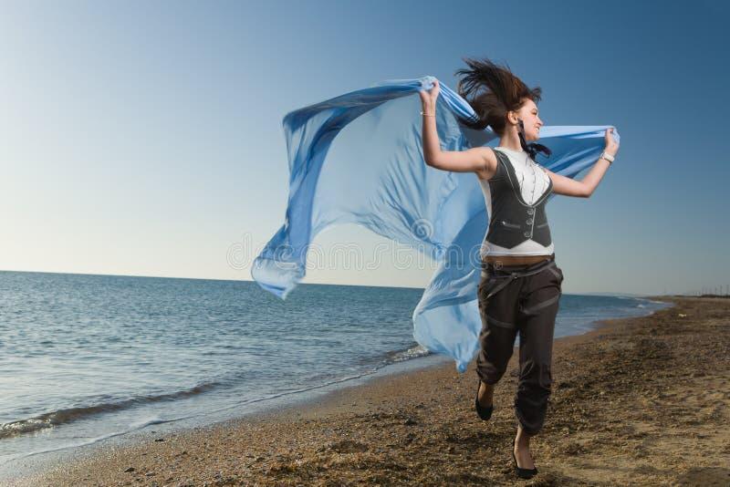 Frohe Frau, die am Seeufer läuft lizenzfreie stockfotografie