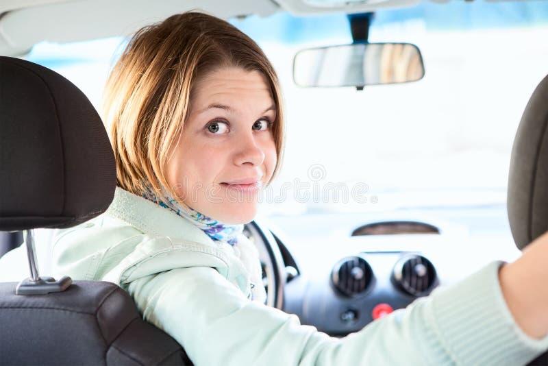 Frohe Frau innerhalb des Autos, das zurück schaut lizenzfreies stockfoto