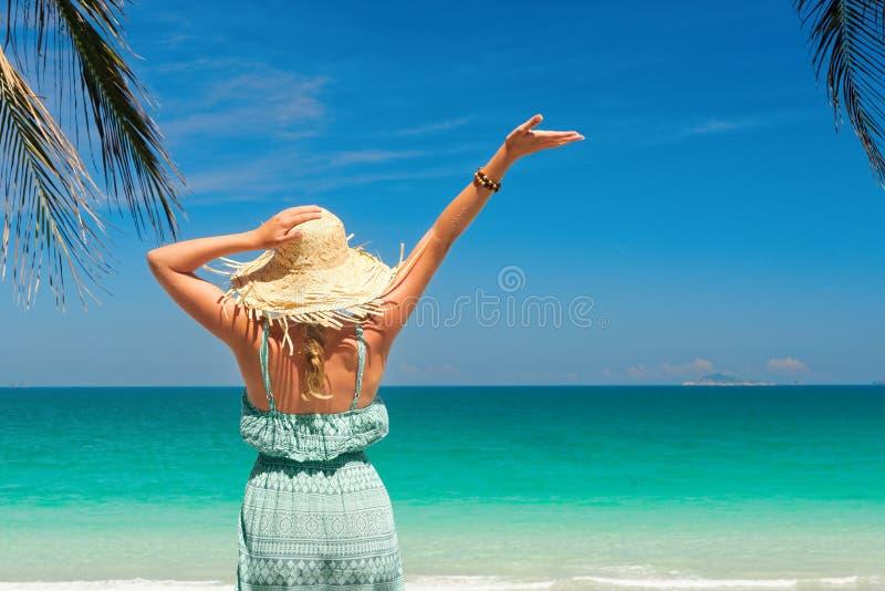 Frohe Frau mit dem Arm oben auf Strand im Sommer während Feiertage trav lizenzfreie stockbilder