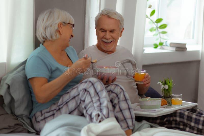 Frohe Gatten, die ein Lachen teilen und Frühstück genießen stockfoto