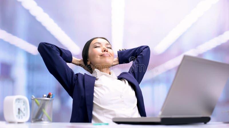 Frohe Geschäftsdame, die auf Stuhlfront des Laptops im Büro, Arbeitsbruch sich entspannt lizenzfreies stockbild