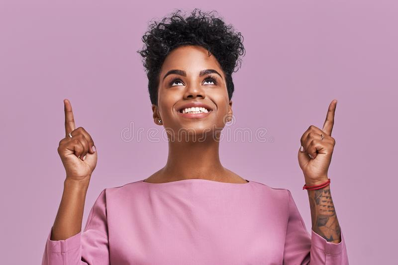 Frohe hübsche Afroamerikanerfrau zeigt mit beiden Vorderfingern oben, hat freundliches Lächeln, dunkle Haut, gelocktes Haar an lizenzfreie stockfotos