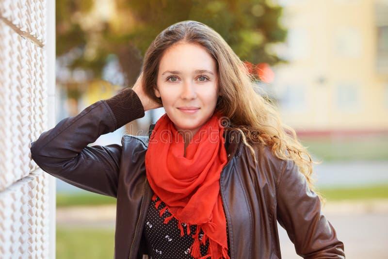 Frohe Jugendmädchenhaltung an der Stadt Damenlebensstil Langes Haar Roter Schal stockbild