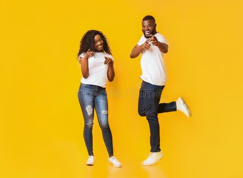 Frohe junge Afropaare, die Finger auf Kamera zeigen stockbilder