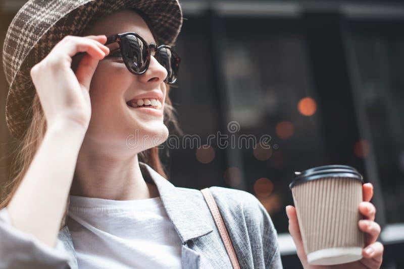 Frohe junge Dame in der Sonnenbrille mit Kaffee draußen stockfotografie
