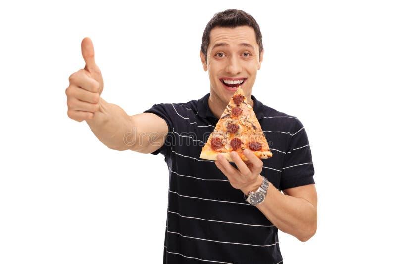 Frohe junge Fleisch fressende Scheibe der Pizza und des aufgeben Daumens stockbild