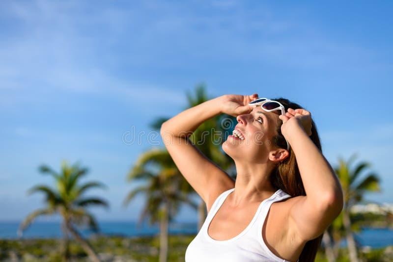 Frohe junge Frau auf tropischer Reise Karibischer Meere, die oben schaut stockfoto