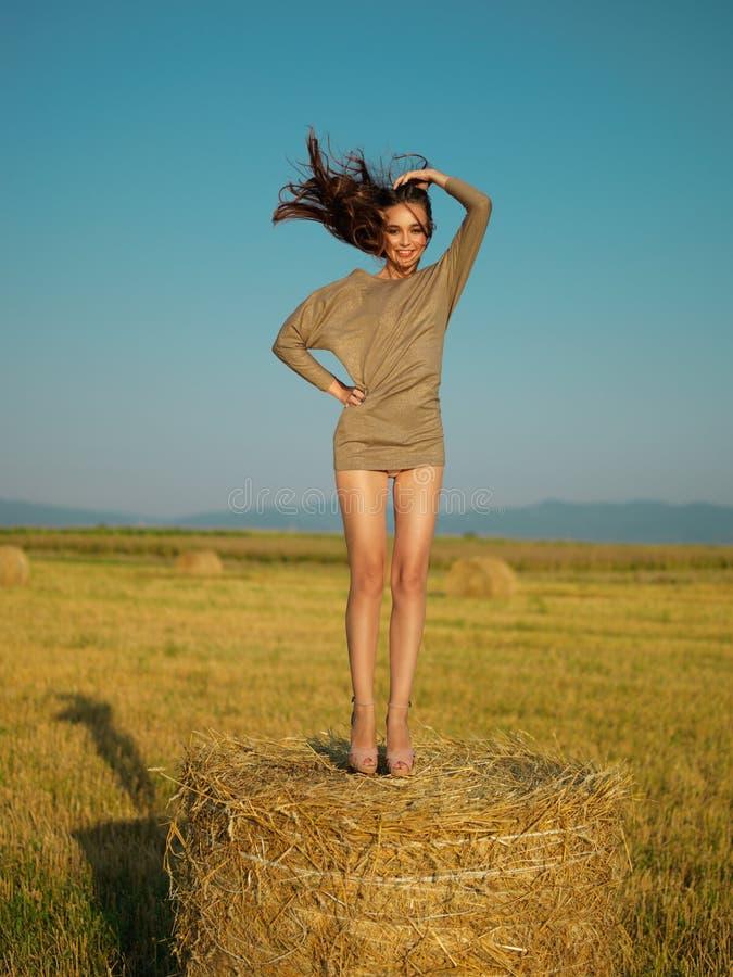 Frohe junge Frau, die auf Heustapel springt lizenzfreie stockfotos