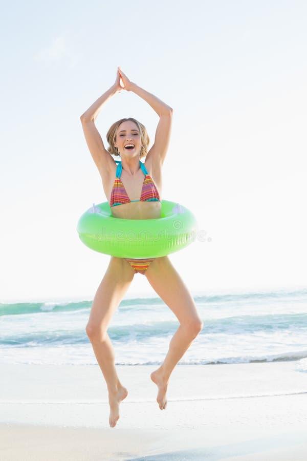 Frohe junge Frau, die einen Gummiring springt auf den Strand hält lizenzfreies stockbild