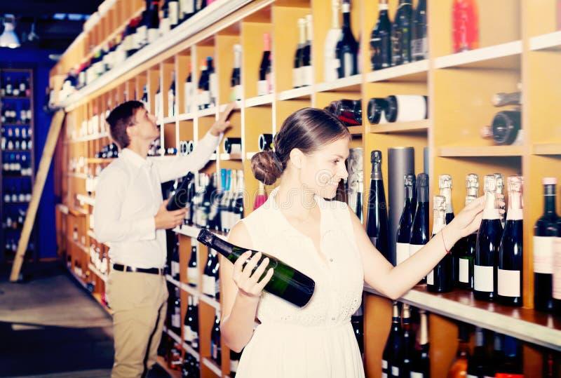 Frohe junge Frau, die Flasche in der Weinhandlung wählt lizenzfreie stockfotos