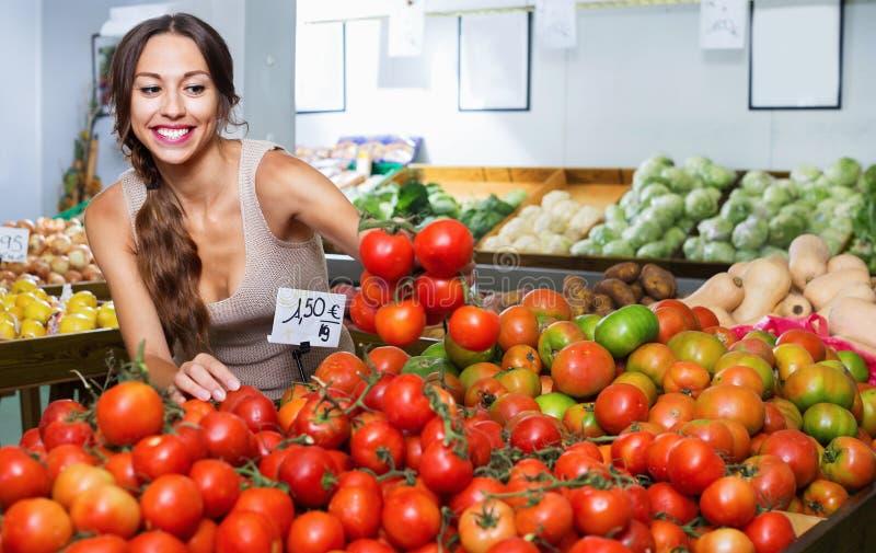 Frohe junge Frau, die frische Tomaten auswählt stockbilder
