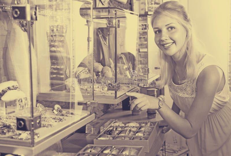 Frohe junge Frau, die Modeschmuck schaut stockfoto