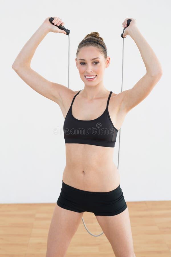 Frohe junge Frau, die Seil für das Überspringen verwendet lizenzfreies stockbild