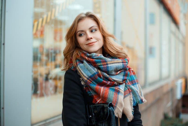 Frohe junge Frau in einem warmen Winterschwarzmantel mit einer Lederhandtasche mit einem woolen modernen warmen Schal in einem Kä lizenzfreie stockfotografie