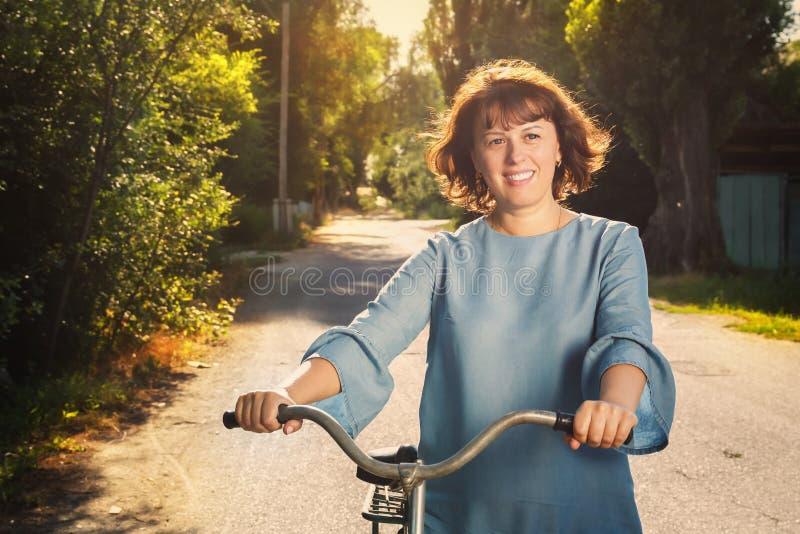 Frohe junge Frau geht nahe bei einem Fahrrad auf einer Landstraße in der Landschaft in den Strahlen des Sonnenuntergangs lizenzfreies stockfoto