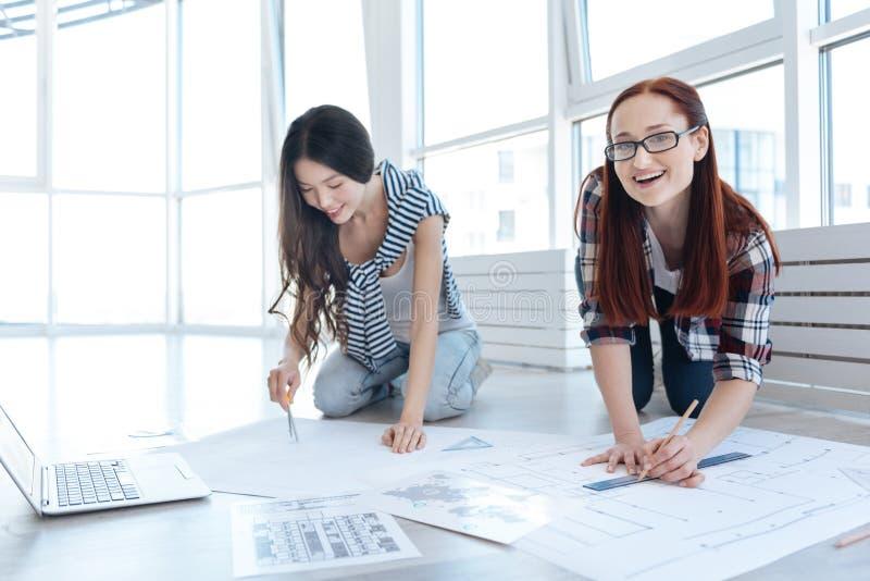 Frohe junge Ingenieure, die an einem Projekt arbeiten stockbilder