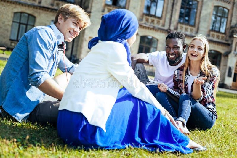 Frohe junge Leute, die draußen zusammen plaudern lizenzfreies stockfoto