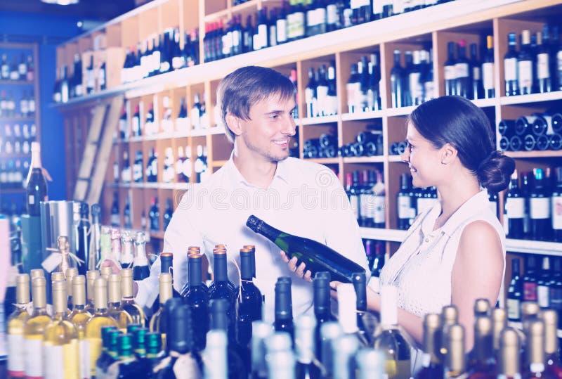 Frohe junge Paare, die zusammen Wein wählen stockfoto