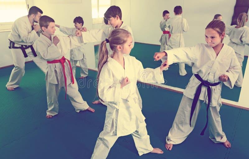 Frohe Kinder, die in den Paaren in der Karateklasse sich auseinander setzen stockbilder