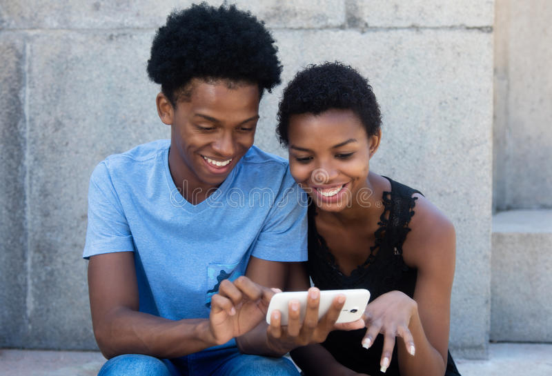 Frohe lachende Afroamerikanerpaare, die Telefon betrachten lizenzfreies stockbild