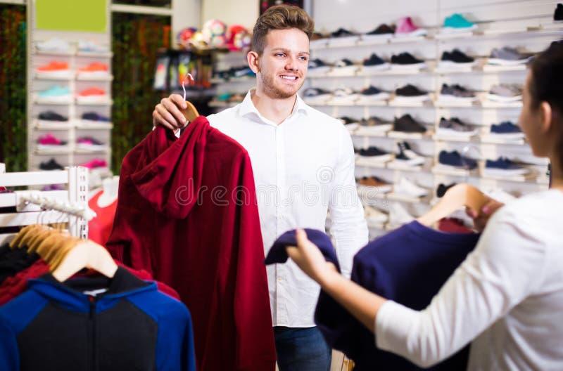 Frohe liebevolle Paare, die auf neuer Sportkleidung entscheiden lizenzfreies stockbild