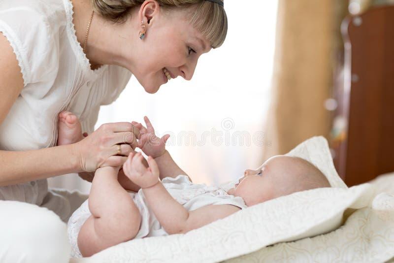 Frohe Mutter, die Gymnastik ihr Babykind spielt und tut stockbild